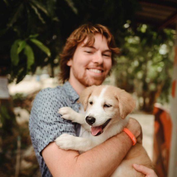 Volunteer with feeding run pup